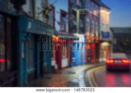 Blurred travel backgrounds - Famous place in Kilkenny, Ireland at night where stand in a row different bars and pubs. It is a popular touristic destination