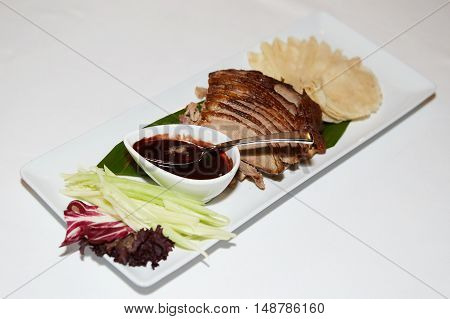 peking duck as served in a restaurant on white plate