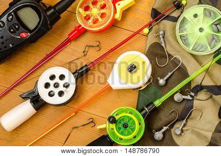 Fishing accessories consisting of tackles radio weights hook net. Wooden background. Outdoor activity and leisure concept.