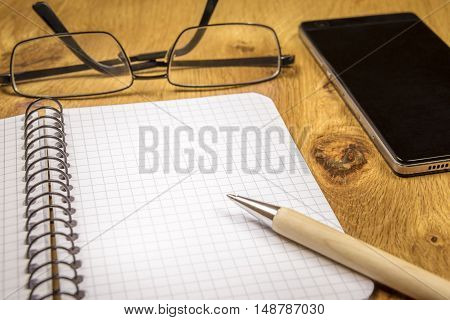 Blank open notebook and a pen on a wooden desk - Close-up image with an opened graph spiral notebook eyeglasses pen and phone on a vintage wooden table. Perfect as a frame or background.