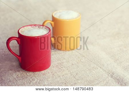 pair of colored mugs with frothy cappuccino stand on a desk / coffee for a couple with mood