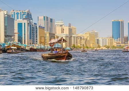 Dubai, United Arab Emirates - May 3, 2013: Traditional Abra ferries along Dubai Creek. The Creek divides the city into two main sections: Deira and Bur Dubai.