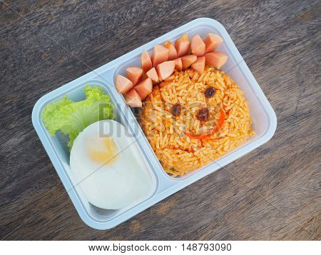 Plastic school lunch box for kids with funny face of fried rice and egg on wood background.Bento packed