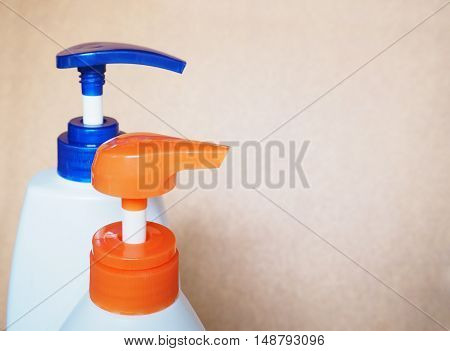 Close up cap of plastic pumping lotion bottle over brown background