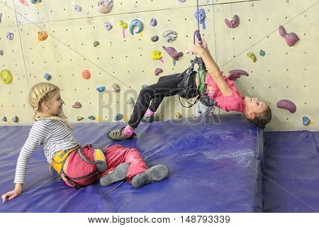 Rock climbing. Two girls in indoor climbing center, one of them hanging on tether