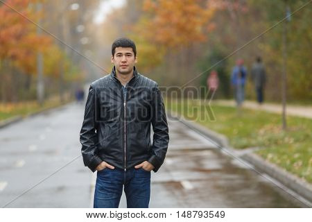 half length portrait of young dark-haired man in black jacket in alley in park