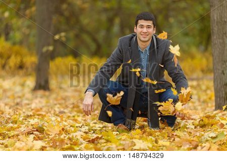 young man in gray coat sitting on his haunches in park and pop-up Yellow maple leaves