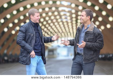 two young man in black jacket on background of lights installation main park alley, talking and gesticulating