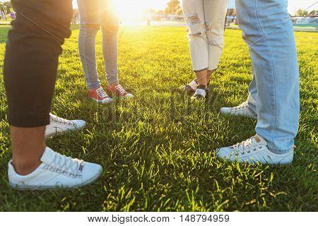 waist down, friends standing on the green grass