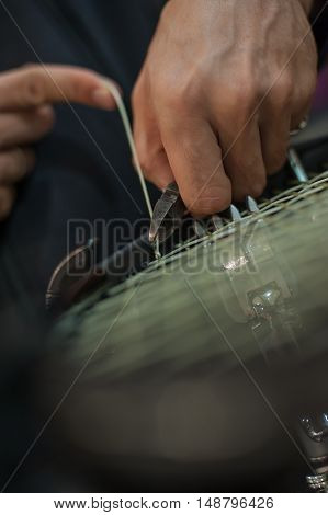Tennis Stringer Tying Knots And Cutting String With Pliers