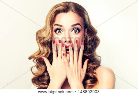 Surprised girl screams and closes  mouth with her  hands from surprise. Presenting your product. Isolated on white background. Expressive facial expressions