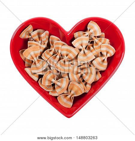 Tomato and Basil Bow Tie Pasta in Heart Shaped Bowl Isolated on white. Selective focus.