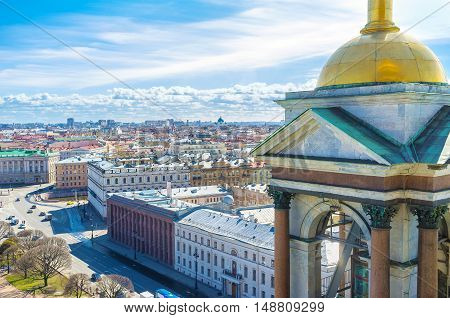 The view on the luxury mansions of St Isaac's Square and old roofs of St Petersburg from the rooftop of St Isaac's Cathedral with its golden domed bell tower on the foreground Russia.