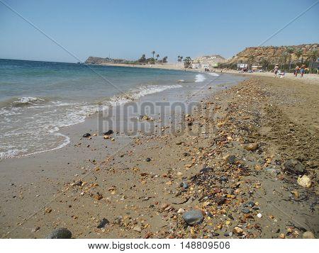 Playa de arena y piedras con mar de fondo