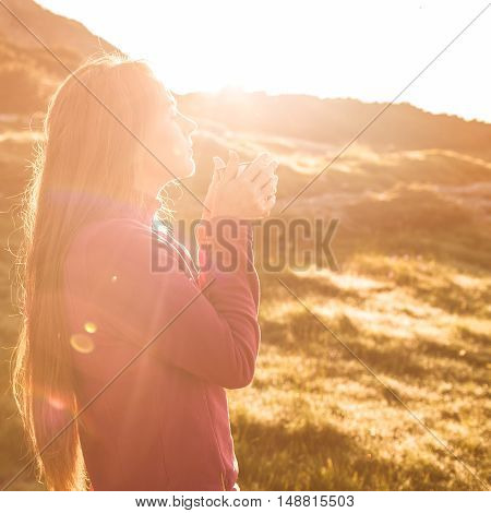 Young woman drinking tea at sunrise in mountains. Mountain camping concept.