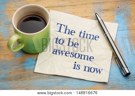 The time to be awesome is now - handwriting on a napkin with a cup of espresso coffee