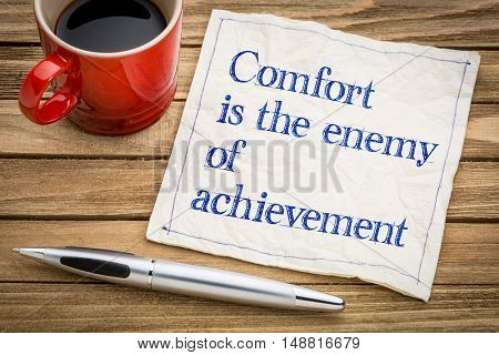 Comfort is the enemy of achievement - handwriting on a napkin with a cup of espresso coffee