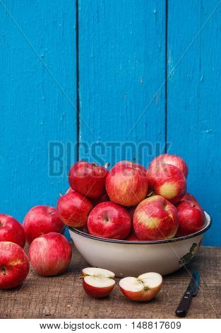 Juicy organic red ripe whole and sliced apples on a wooden table on a blue background. A rustic style. Selective focus