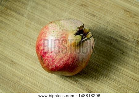 Fruit pomegranate shot on a textured wooden surface