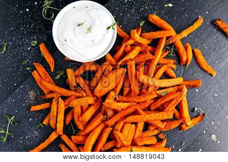 Healthy Homemade Baked Orange Sweet Potato Fries with fresh cream dip souce, herbs, salt and pepper