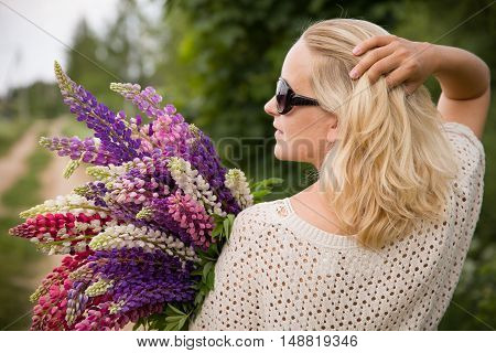 Smiling young girl holding a bunch of beautiful lupine flowers. Purple and pink lupin bouquet. Womanl with bouquet of wild lupin flowers on sunny summer field.