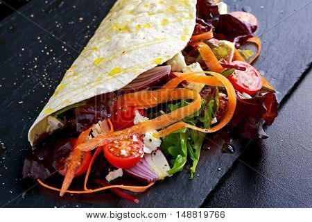 Vegetarian tortillas taco wrap with red onion, sweet cherry tomatoes, carrots, ruby red chard, rocket and feta chees drizzled with olive oil.