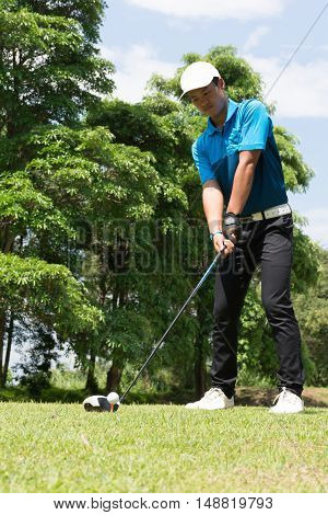 Handsome asian golfer man putt golf .
