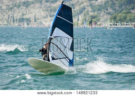 Young man surfing on the lake with wind