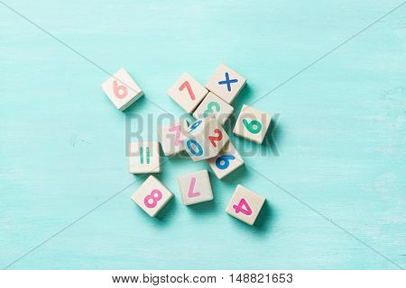 Wooden cubes with numbers on a turquoise wooden background.