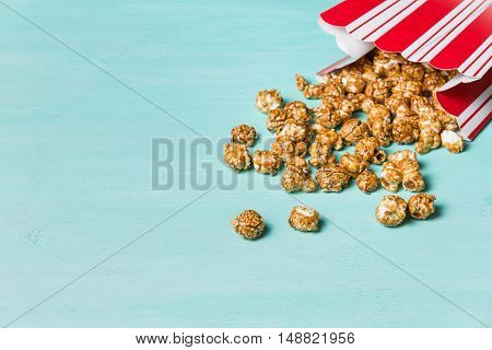Popcorn on turquoise background. Caramel pocorm in the red and white cup. Cinema. Movie time.