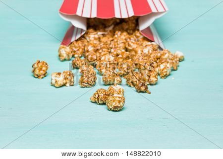 Popcorn on turquoise background. Caramel pocorn in the red and white cup. Cinema. Movie time.