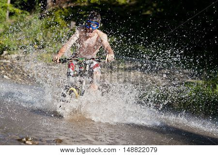 Extreme mountainbiker rides in to the water