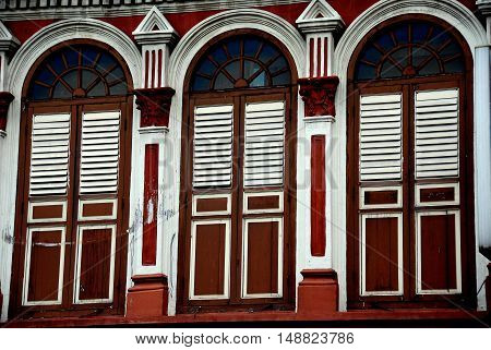 Singapore - December 16 2007: Handsome fan windows with wooden louvered shutters adorn a 19th century Chinese shop house in Little India *
