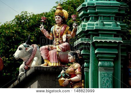 Singapore - December 18 2007: Goddesses holding lotus flowers and a sacred cow decorate a gateway at the Sri Veeramakaliamman Hindu Temple in Little India
