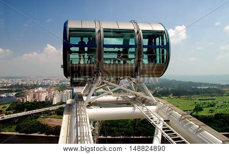 Singapore - December 18 2007 : Passengers riding in one of the gondolas high atop the Singapore Flyer ferris wheel view a vast panorama *