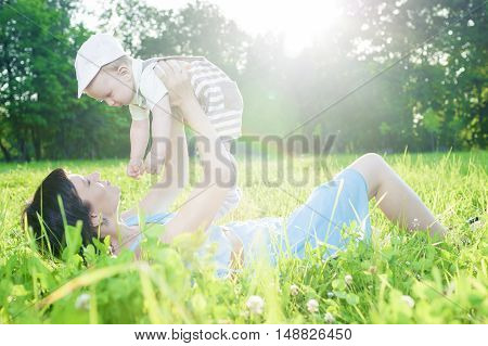 Portrait of Mother with Her Adorable Cute Son Against Nature Background. Horizontal Image Orientation