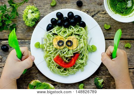 Food art idea for kids green monster from spaghetti olives and bell pepper. Child eating concept top view