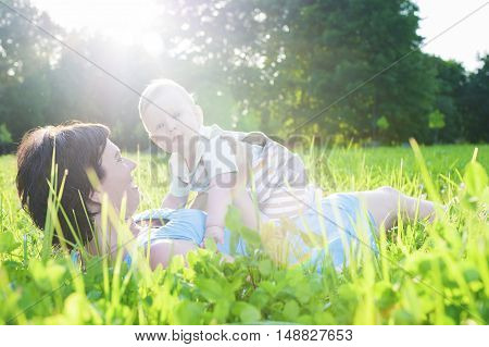 Family Life Concepts. Portrait of Mother with Her Toddler Son Playing Outdoor in Park. Horizontal Image
