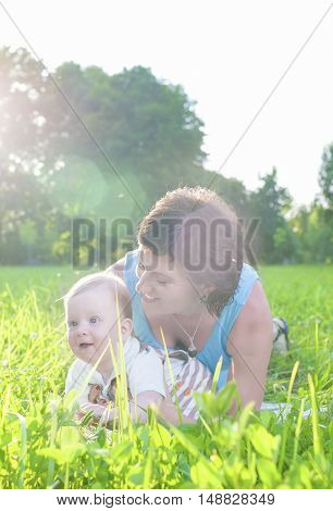 Happy Family Life Concepts and Ideas. Caucasian Brunette Mother with Her Toddler Son Spending Time Together Outdoors Embraced in Park. Vertical Image