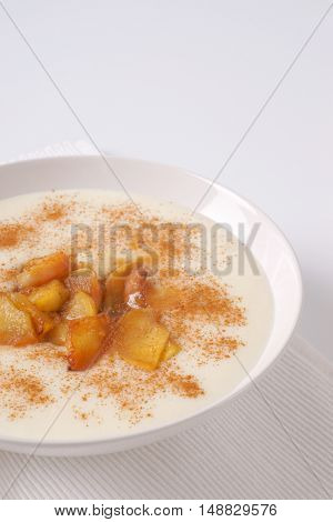 plate of semolina pudding with apples and cinnamon on white place mat