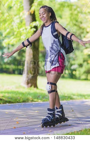 Sport and LIfestyle Concepts. African American Teenager Learning Roller Skating While Ballancing with Hands Outdoors Vertical Image