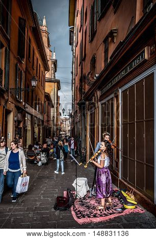Bologna Italy 18 September 2016: two buskers violinists perform for the passersby in the historic district of Bologna before the storm.