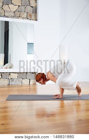 Yoga Crow Pose in wooden floor gym and mirror indoor