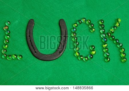 The word luck spelled with marbles and a horse shoe on a green background for St. Patrick's day
