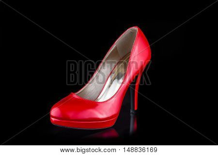 Single red woman high heel shoe isolated on black background