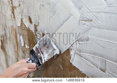 Align the wall with a painting ground coat painter hands holding spatula close-up.