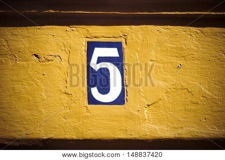 Enamelled tile door number five on yellow plaster wall