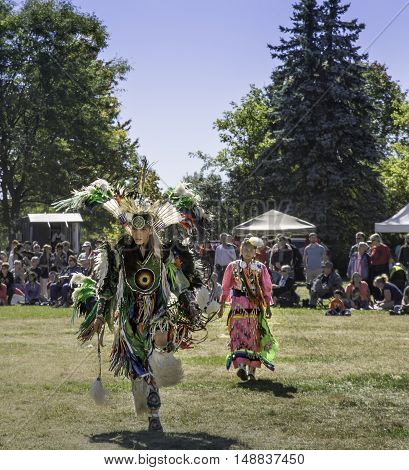 WATERLOO, ONTARIO - SEPTEMBER 24, 2016: Dancers in traditional aboriginal costume dance to the beat of drums in a Pow Wow at Waterloo Park. This is the 13th annual Pow Wow hosted by the Waterloo Aboriginal Education Centre.