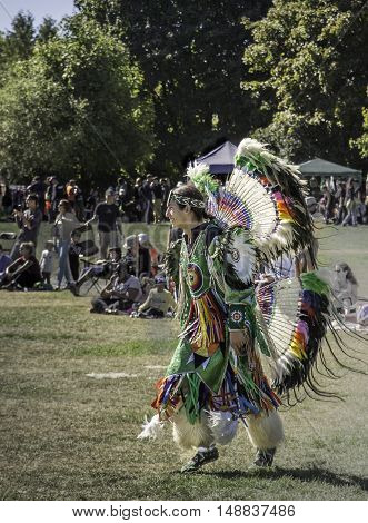 WATERLOO, ONTARIO - SEPTEMBER 24, 2016: A dancer in traditional aboriginal costume dances to the beat of drums in a Pow Wow at Waterloo Park. This is the 13th annual Pow Wow hosted by the Waterloo Aboriginal Education Centre.