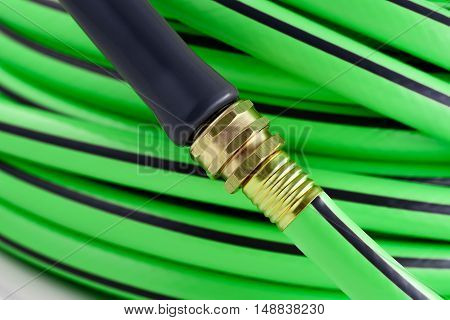 Green garden hose brass nozzle attached close-up